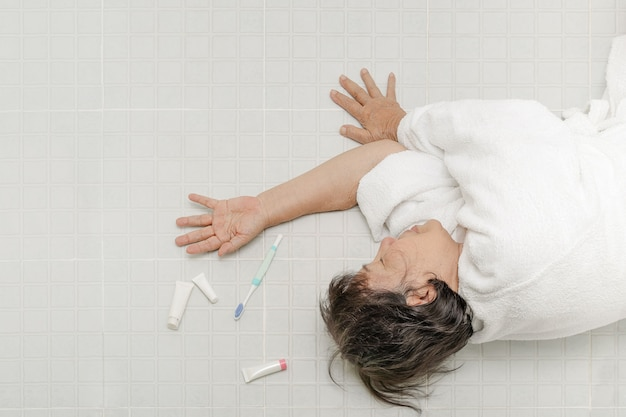 滑りやすい表面のために浴室に落ちる高齢者の女性