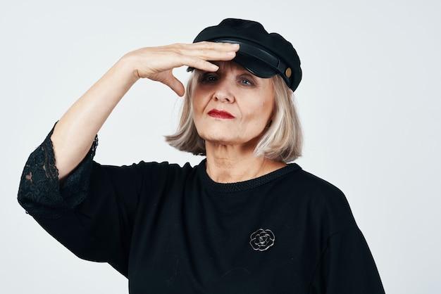Elderly woman in fashionable clothes black hat studio posing