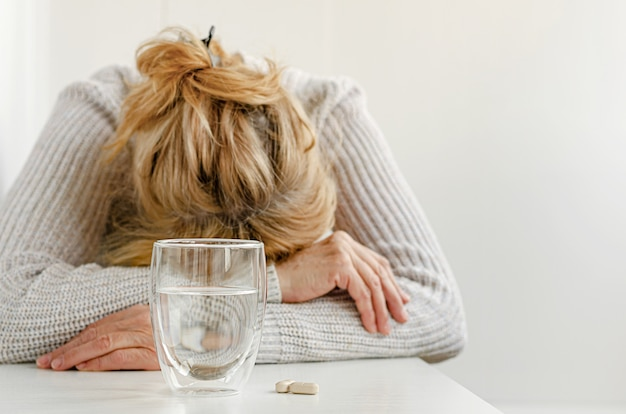 Elderly woman feeling stressed. selective focus on glass and pills. depression treatment concept