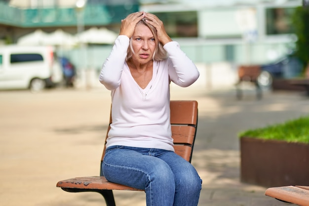 노인 여성은 거리의 벤치에 앉아 기분이 나쁘다