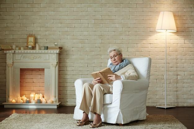 Пожилая женщина сосредоточена на чтении