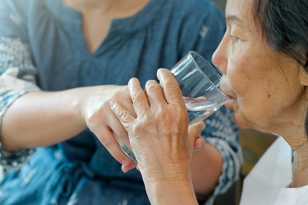 Elderly woman gets a glass of water from caregiver
