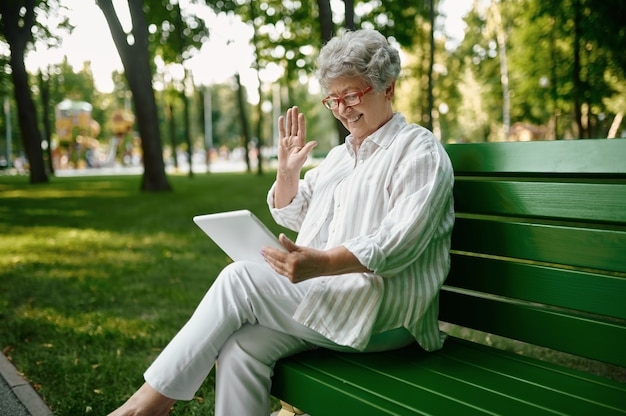 An elderly woman in glasses using laptop on bench
