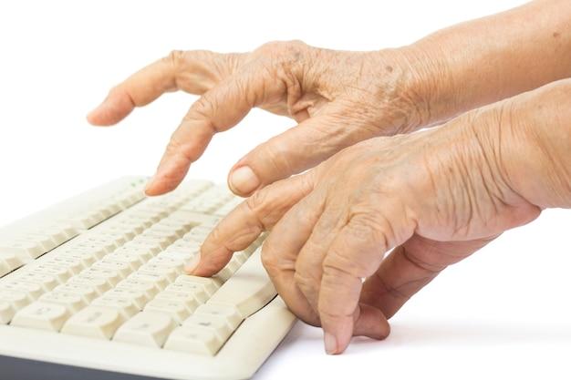 Пожилая женщина руки на клавиатуре компьютера Premium Фотографии