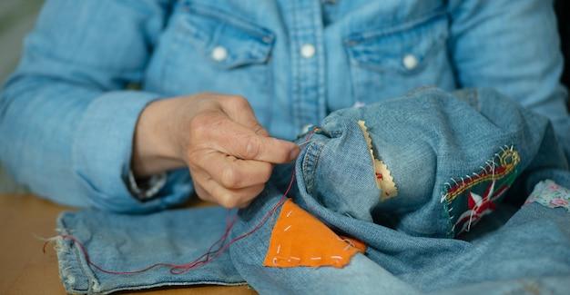 Пожилая женщина руки шить ткань джинсов