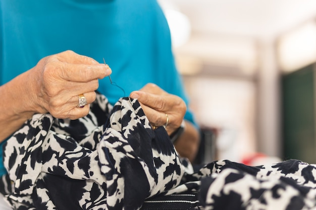 Elderly woman hands using needle and thread to mend a dress