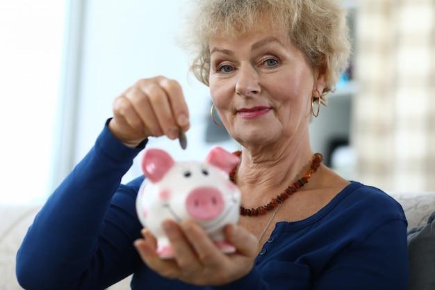 Пожилая женщина счастливо копит деньги в копилку.