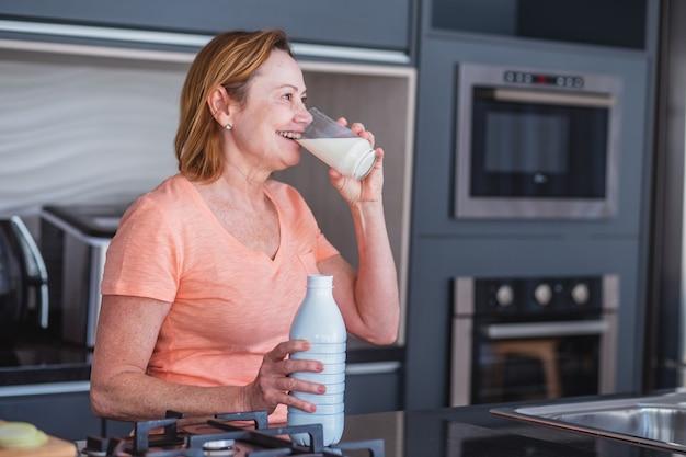 아침에 우유 한 잔을 마시고 있는 할머니.