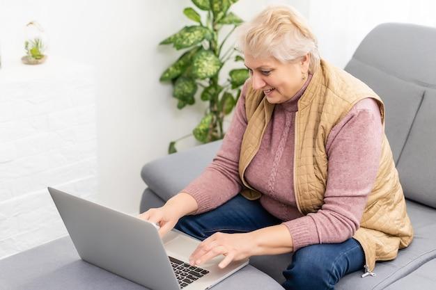 Пожилая женщина во время видеозвонка со своей семьей, улыбается и машет рукой. карантинное время.