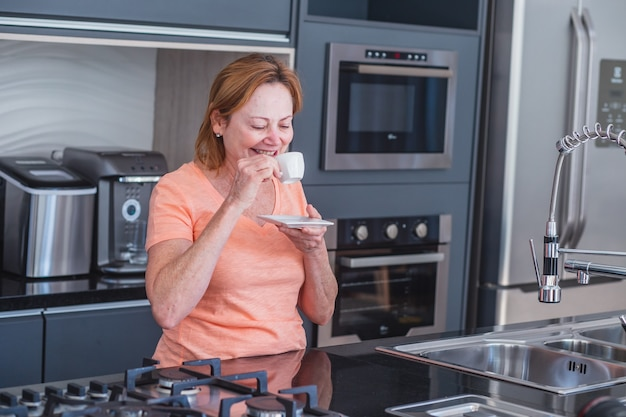 Elderly woman having a cup of coffee or tea in the kitchen when she wakes up.