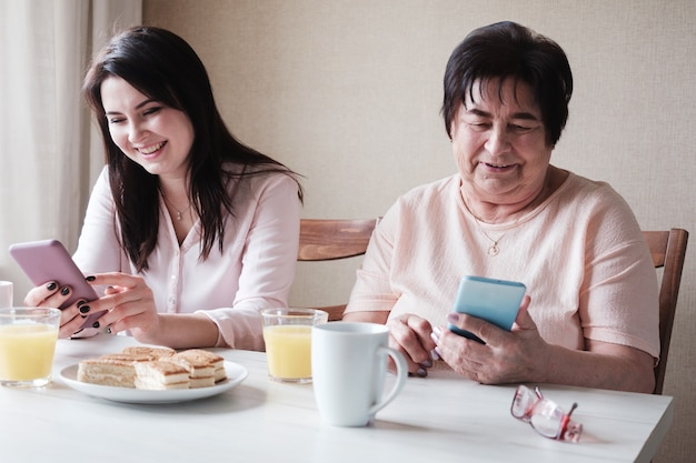 An elderly woman and her daughter use the phone to exchange messages