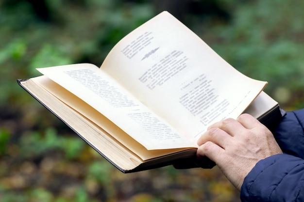自然の森の中で本を持つ年配の女性。野外レクリエーション