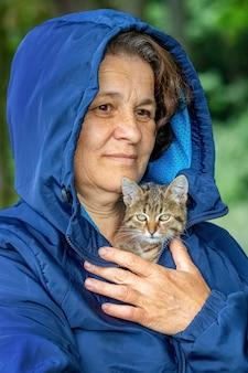 작은 줄무늬 고양이를 안고 있는 할머니, 여자의 팔에 새끼 고양이