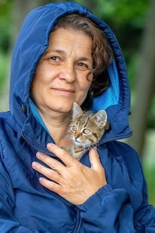 小さな縞模様の子猫を抱いている年配の女性。女性はジャケットの下で寒さから子猫を隠します