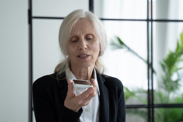 Пожилая женщина держит смартфон во время записи голосового сообщения своему другу. современный пожилой офисный служащий подносит смартфон ко рту и записывает голосовое сообщение.