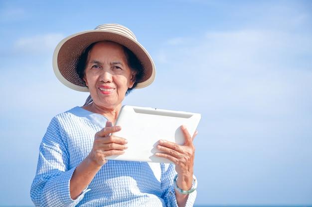 Пожилая женщина держит планшет сделайте видеозвонок через интернет, чтобы поговорить со своим ребенком. концепция счастливого выхода на пенсию