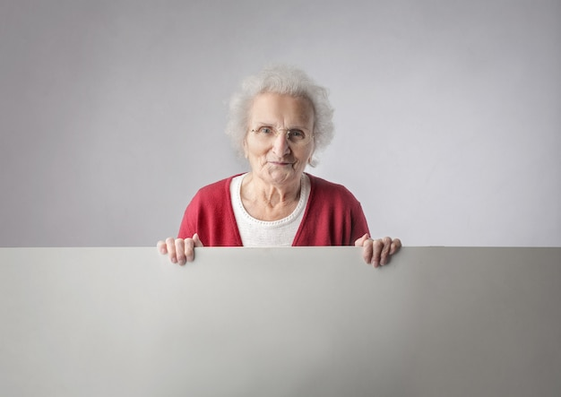 Elderly woman holding a board