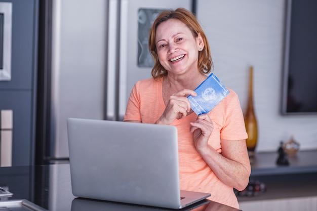 ブラジルのワークカードとコンピューターを保持している年配の女性。ホームオフィスのコンセプトでワークブックを保持している年配の女性。