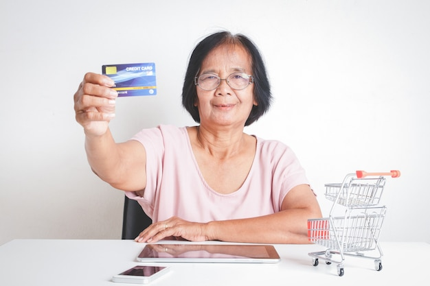 An elderly woman holding a credit card