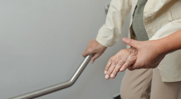 Elderly woman holding on handrail with caregiver