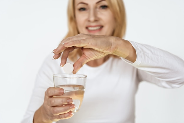 Elderly woman holding medicine and looks into the camera