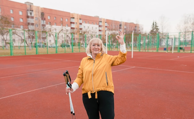 An elderly woman holding a nordic walking stick stands at the stadium on a red treadmill. healthy lifestyle of old people