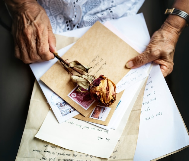 Elderly woman holding old letters with dry rose in her hands