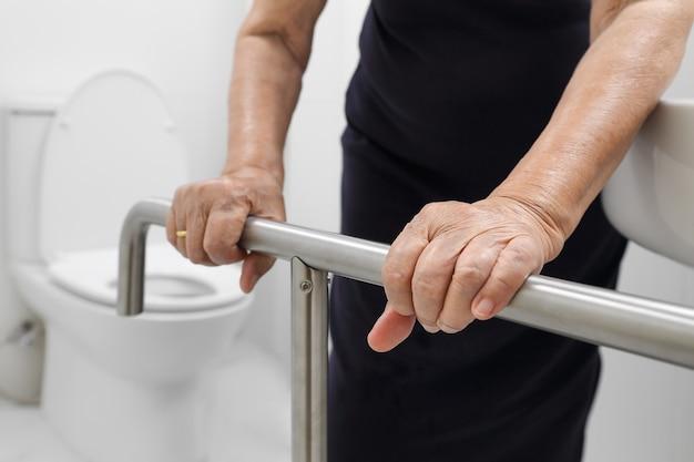 Пожилая женщина, держащая поручень в туалете.