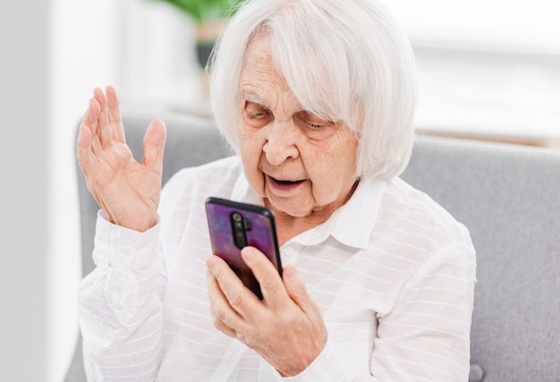 Elderly woman holding smartphone at her hand and looking at screen