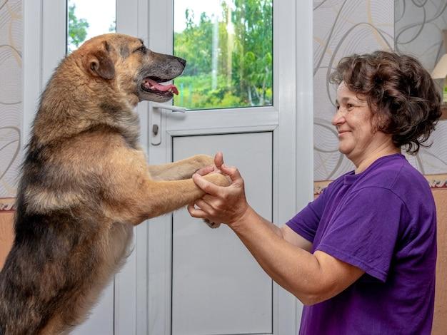 大好きな犬の足を持った年配の女性。