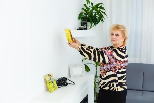 할머니가 손자의 사진 캔버스를 들고 있다