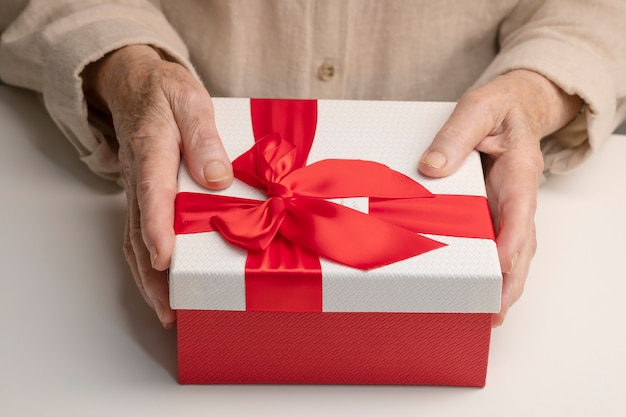 An elderly woman holds holiday box. the style of living of pensioners. caring for the elderly. Premium Photo