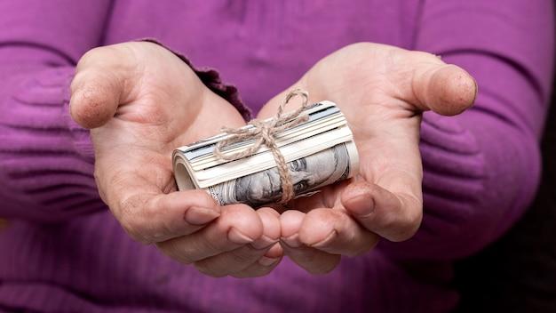 年配の女性は彼女の手にお金を持っています