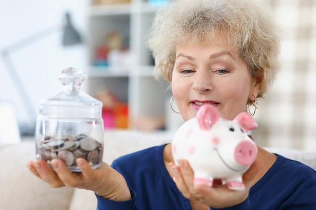 노인 여성은 그녀의 손에 돼지 저금통과 동전 항아리를 보유