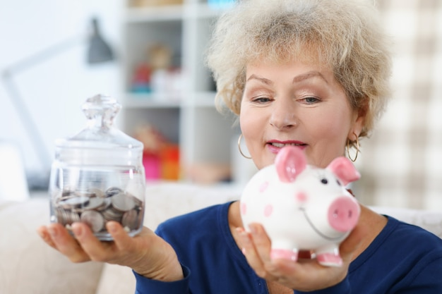 Elderly woman holds piggy bank and jar of coins in her hands