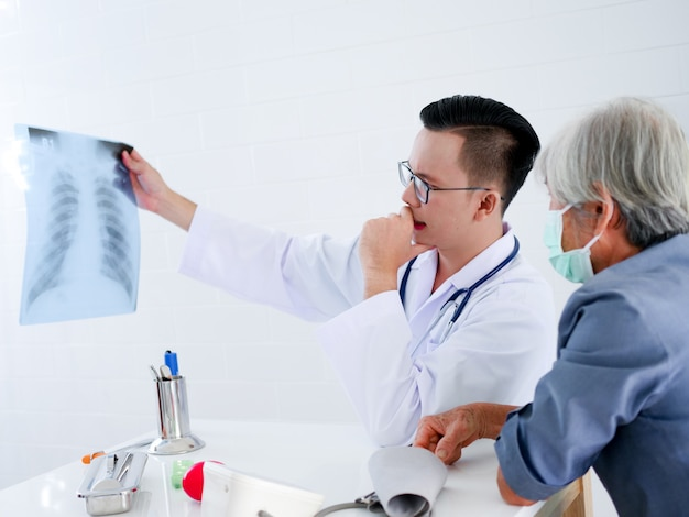 Elderly woman in hospital with doctor holding x-ray film in hands .health care concept.