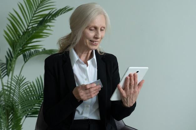 Пожилая женщина в деловом костюме сидит в кресле и использует планшет