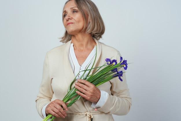 Пожилая женщина в халате с букетом цветов памяти заботы
