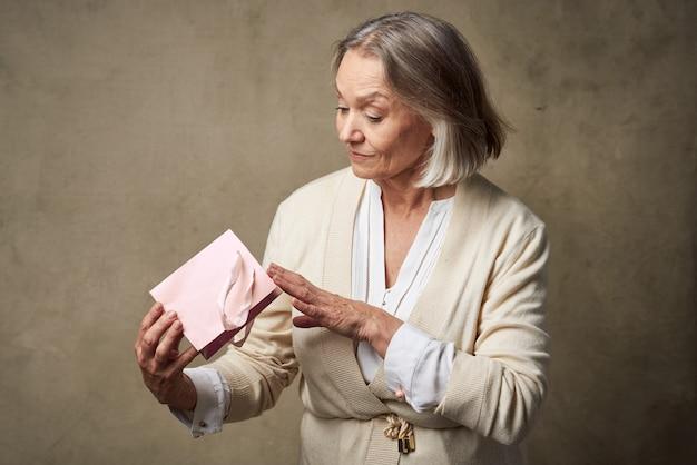 Пожилая женщина в халате с подарком в руках уход за днем рождения