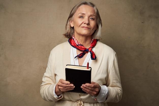 Пожилая женщина в халате с записной книжкой в руках студии