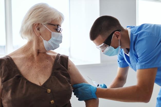Пожилая женщина в медицинской маске в больнице на приеме у врачей, паспорт вакцины