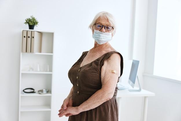 백신을 든 팔에 반창고가 있는 의료용 마스크를 쓴 할머니