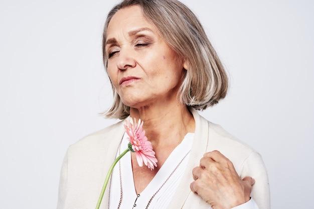 花の贈り物の光の背景を保持しているローブの老婆