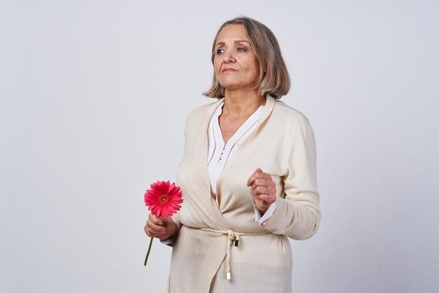 Пожилая женщина в халате с цветочным подарком на светлом фоне