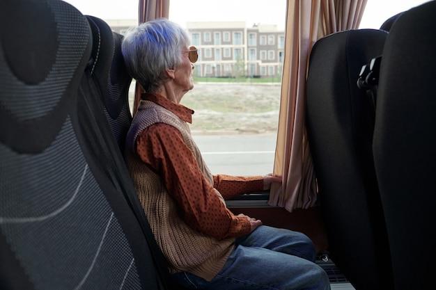 Пожилая женщина в повседневной одежде смотрит в окно, сидя в автобусе