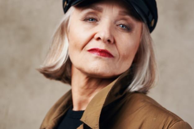 Пожилая женщина в пальто позирует модном осеннем стиле