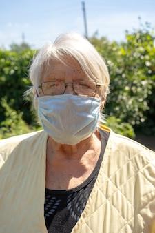 フェイスマスクを身に着けている彼女の庭の老婆