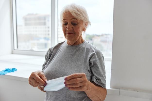手健康保護の医療マスクと病院の年配の女性