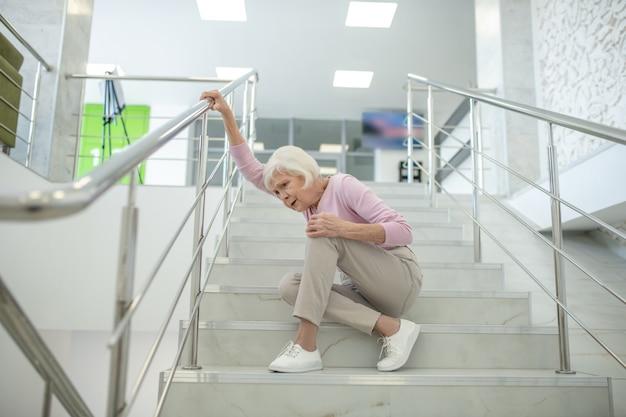 ピンクのシャツを着た年配の女性が階段に落ちる