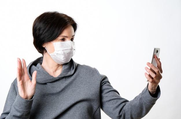 防護マスクの高齢女性が電話で話しています。